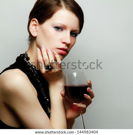 Young woman with a wineglass near the wall, isolated on grey - stock photo