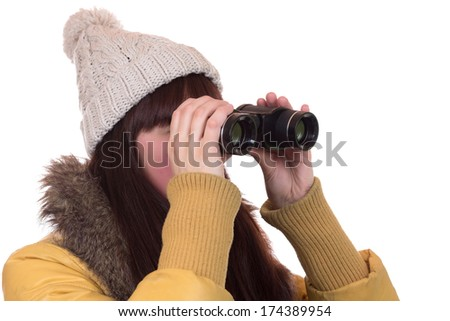 Young woman with a winter cap looking through binoculars, isolated on a white background