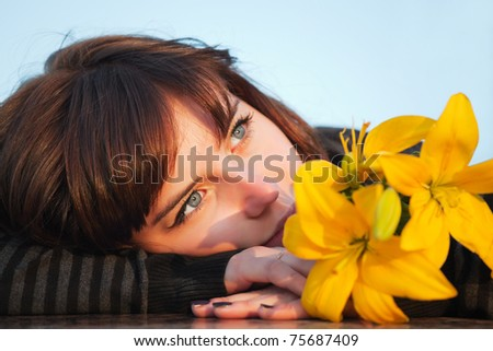 Young woman with a yellow lilies - stock photo
