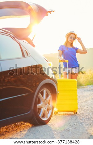 Young woman with a yellow suitcase standing near the trunk of a car parked on the roadside