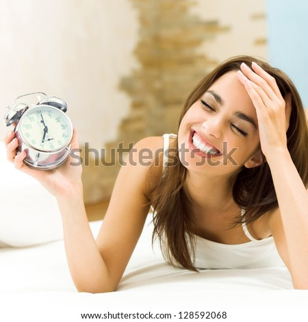 Young woman with alarmclock on the bed at the morning - stock photo