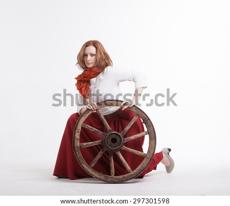 young woman with an old wagon wheel on white background - stock photo
