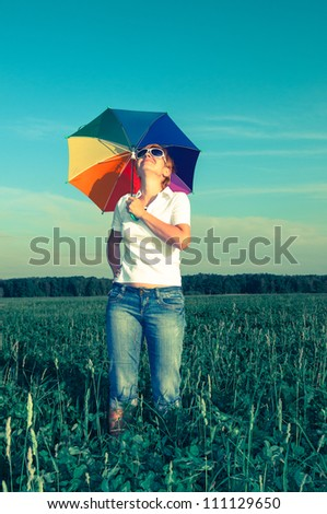 young woman with an umbrella on the field - stock photo