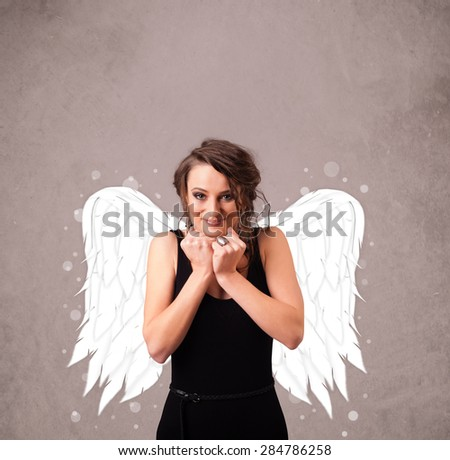 Young woman with angel illustrated wings on grungy background - stock photo