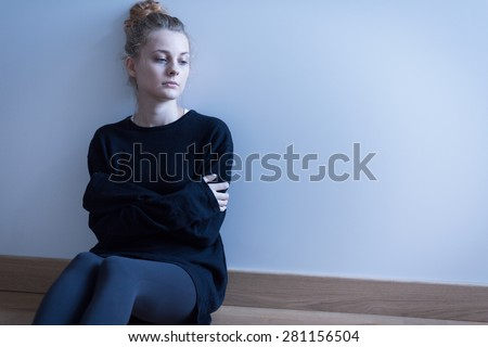 Young woman with anxiety disorder sitting on the floor - stock photo