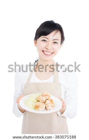 young woman with apron holding fried chicken, isolated on white background - stock photo