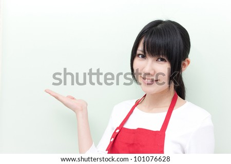 young woman with apron showing copy space - stock photo