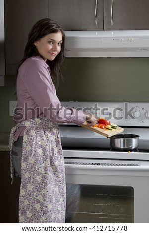 Young woman with apron, standing in front of the stove, putting cut vegetable in a pot