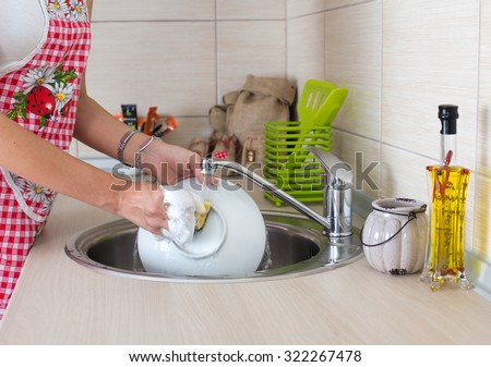 Young woman with apron washing dishes in modern kitchen - stock photo