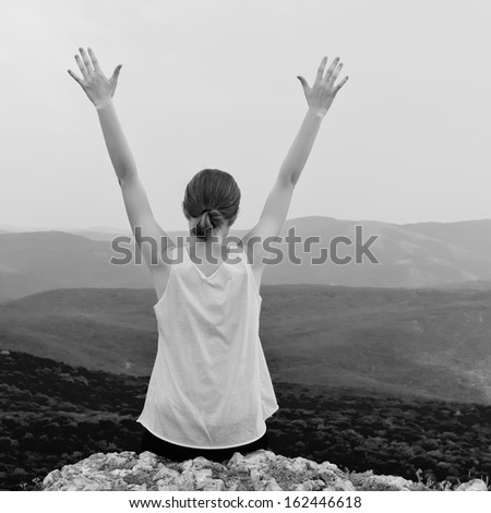 Young woman with arms raised. Girl sitting on a cliff side - stock photo