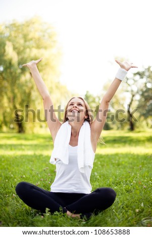 Young woman with arms raised sitting in park after training.