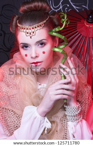 Young woman with artistic visage and hairstyle and with bamboo