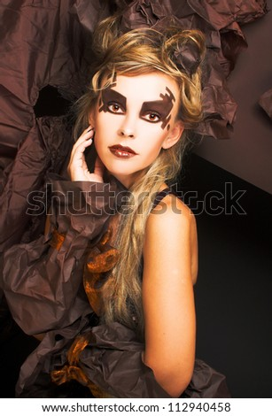 Young woman with artistic visage and in creative image in brown tones. - stock photo