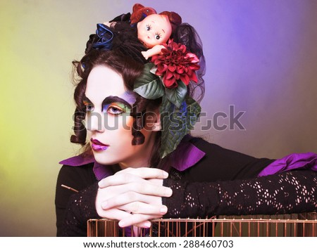 Young woman with artistic visage and with original hairstyle with dolls and flowers.