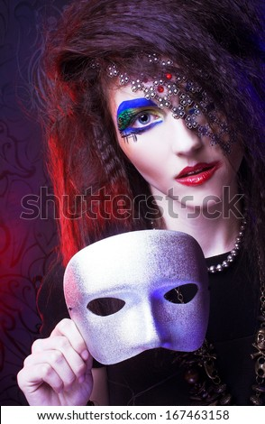 Young woman with artistic visage posing with silver mask - stock photo