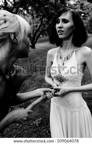 young woman with aspen pole killing witch - stock photo