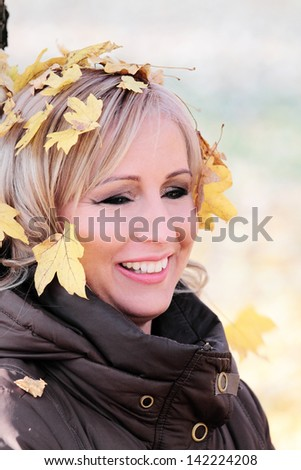 Young woman with autumn leaves - stock photo