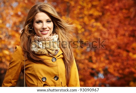 Young woman with autumn leaves in hand and fall yellow maple garden background - stock photo