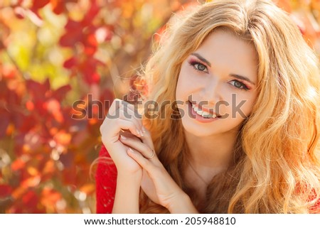 Young woman with autumn leaves in hand and fall yellow maple garden background. Autumn bright portrait.  - stock photo