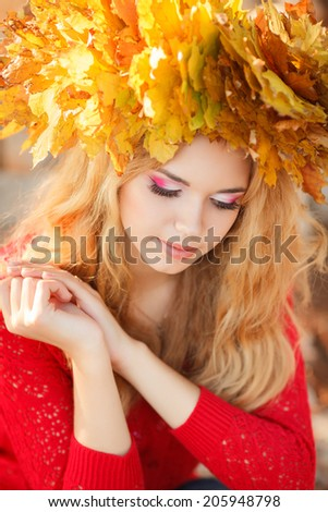 Young woman with autumn leaves in hand and fall yellow maple garden background. Woman with wreath of yellow leaves on head. Autumn bright portrait.  - stock photo