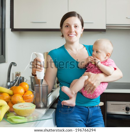 Young woman with baby girl cooking fruit puree in kitchen