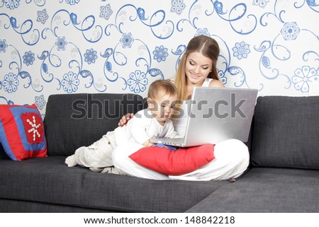 young woman with baby working with laptop at home - stock photo