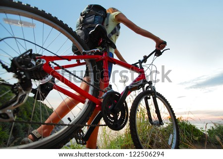 Young woman with backpack and bicycle walking on countryside terrain - stock photo