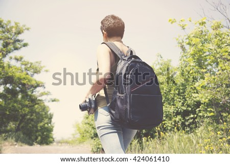 young woman with backpack and camera - stock photo