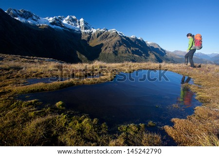 Young woman with backpack at mountain lake - stock photo