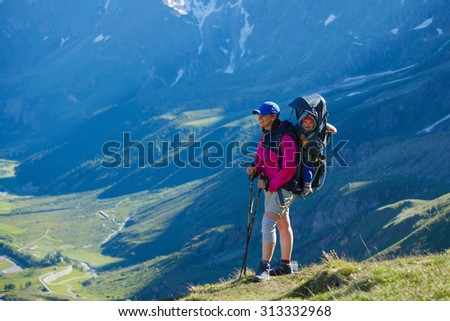 Young woman with backpack child carrier and a smiling baby boy inside it while hiking, Breuil-Cervinia, Italy - stock photo