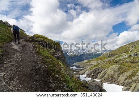 Young woman with backpack climbing in highland trail, scenic mountains on background - stock photo