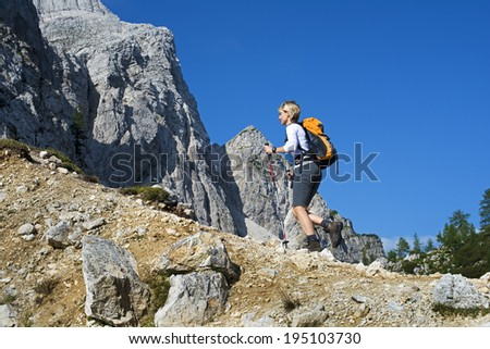 Young woman with backpack hiking in mountains - stock photo
