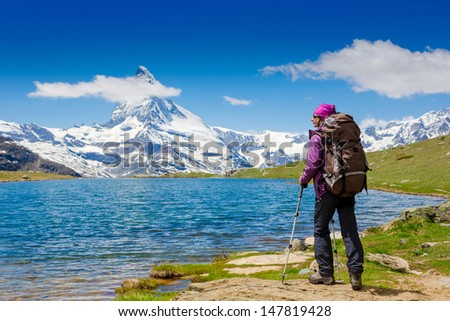 Young woman with backpack hiking in the mountains. Alps - stock photo
