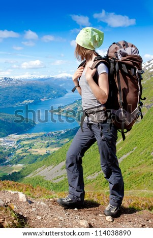 Young woman with backpack hiking in the mountains. Norway - stock photo