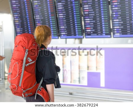Young woman with backpack in airport near flight timetable - stock photo
