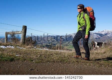Young woman with backpack in the mountains - stock photo