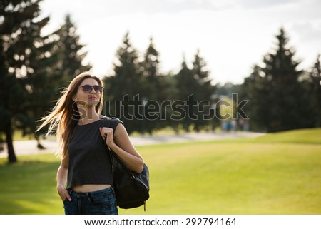 Young woman with backpack in the park - stock photo