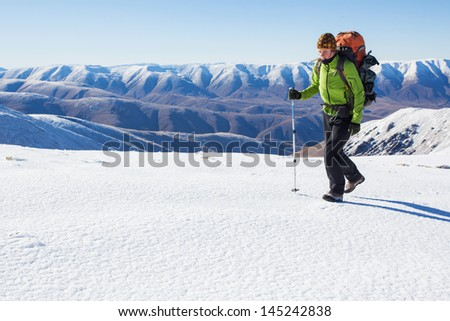 Young woman with backpack in winter mountains - stock photo