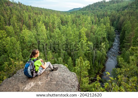 Young woman with backpack look at green forest and river from high point of view. Blurred background