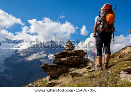 Young woman with backpack on a mountain trek - stock photo