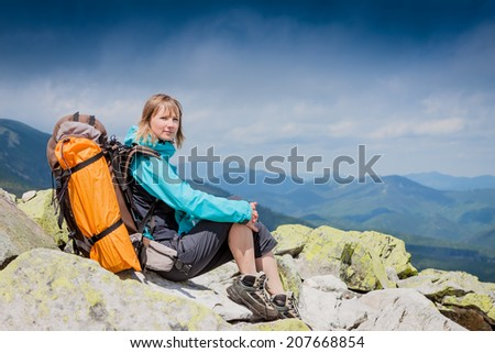 Young woman with backpack sitting on cliff and looking away  - stock photo