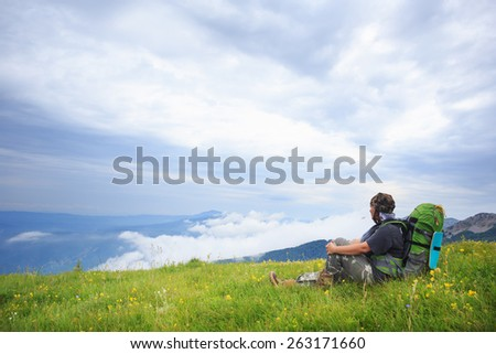 Young woman with backpack sitting on field with green grass and flowers under a blue summer sky and looking at the beautiful mountain landscape - stock photo