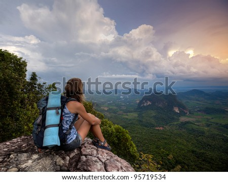 Young woman with backpack sitting on top of a mountain and enjoying sunset valley view - stock photo