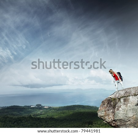 Young woman with backpack standing on cliff's edge and looking down