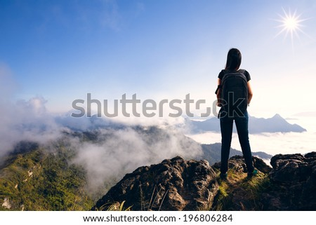 Young woman with backpack standing on cliff's edge and looking to a sky - stock photo