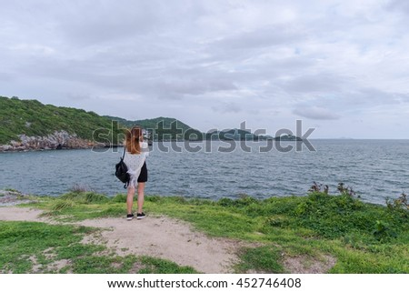 Young woman with backpack standing on cliff's edge and taking a photo