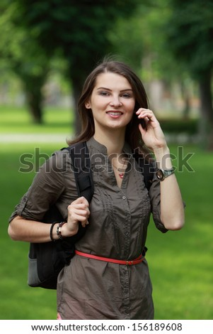 Young woman with backpack using a mobile phone in a park.