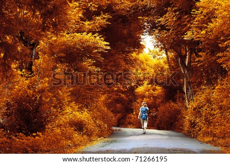 Young woman with backpack walking on a wet asphalt path in a park. Toned - stock photo