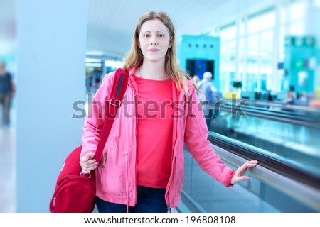 Young woman with bag in airport. - stock photo