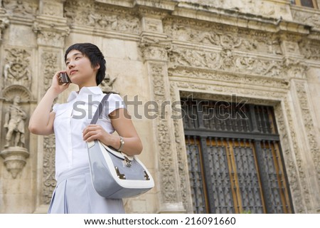 Young woman with bag using mobile phone outdoors, low angle view - stock photo